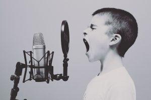 Verklaring spreken schreeuwen jongen microfoon zwart wit